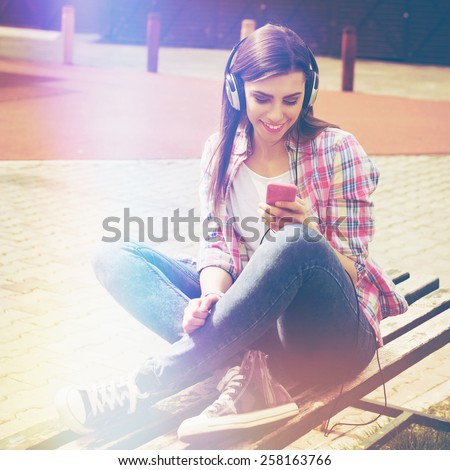 Happy teenage girl in jeans and plaid pink shirt with smartphone and headphones in park in spring. Young woman in casual outfit sitting in park listening to music. Retouched, filter, square format. - stock photo