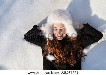 Happy teenage girl lying in the deep snow on beautiful winter day. - stock photo