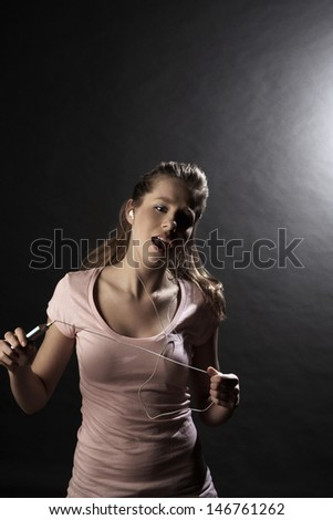 Happy teenage girl singing while listening music through MP3 player on gray background - stock photo