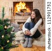 happy teenage girl sitting near christmas tree - stock photo