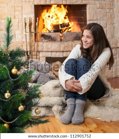 happy teenage girl sitting near christmas tree