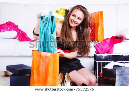 Happy teenage girl taking new dress out of the bag - stock photo