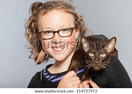 Happy teenage girl with glasses and blond curly hair hugging dark brown eastern shorthair cat. Studio shot isolated on grey background. - stock photo