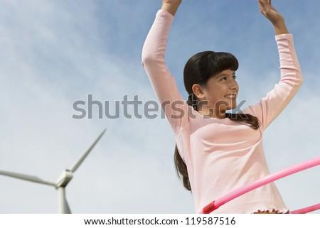 Happy teenage girl with hula hoop looking away against cloudy sky - stock photo