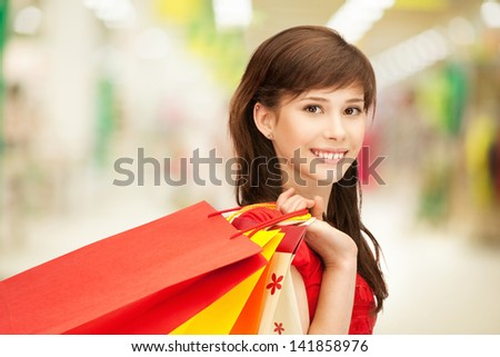 happy teenage girl with shopping bags at the mall - stock photo