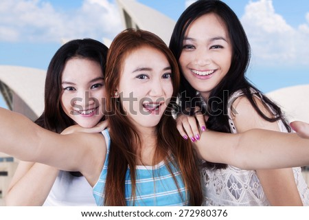 Happy teenage girls taking self photo together while smiling at the camera, shot at Opera House - stock photo
