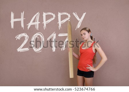 Happy 2017 - Teenage long haired girl in red sleeveless tank top and black shirts posing with huge pencil in hand near wall with text message
