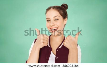 happy teenage student girl showing thumbs up - stock photo