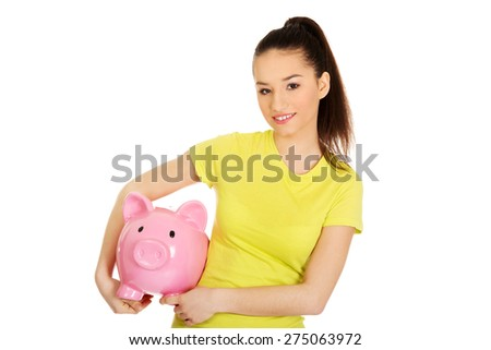 Happy teenage woman holding piggybank. - stock photo
