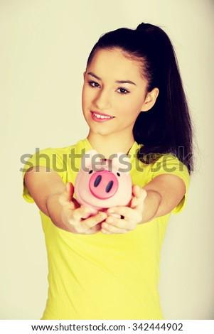 Happy teenage woman holding piggybank. - stock photo