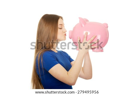 Happy teenage woman kissing piggybank. - stock photo