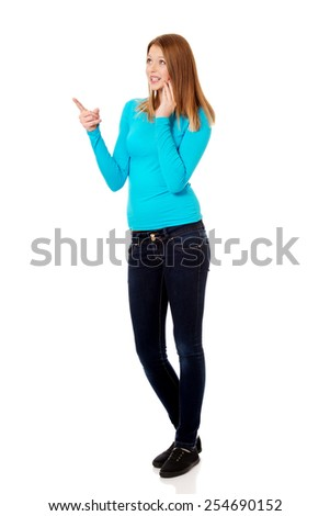 Happy teenage woman pointing up - stock photo
