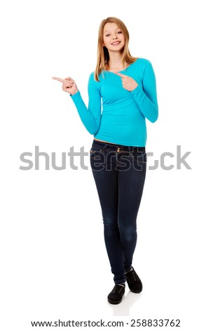 Happy teenage woman pointing with both hands - stock photo