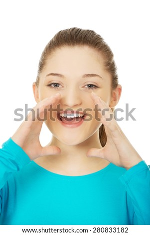 Happy teenage woman whispering a gossip. - stock photo