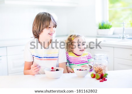 Happy teenager boy and his cute toddler sister having fruit and cereal with strawberry for breakfast before school and kindergarten in a sunny white kitchen with a window  - stock photo