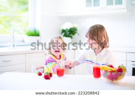 Happy teenager boy and his cute toddler sister having fruit for breakfast before school and kindergarten drinking juice in a sunny white kitchen with a window  - stock photo