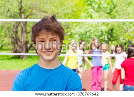 Happy teenager boy on playground during volleyball - stock photo