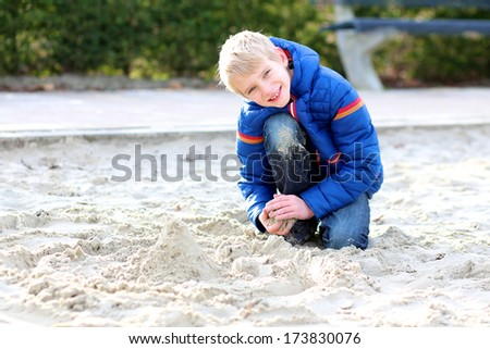 Happy teenager boy relaxing after school at the playground building sand castle