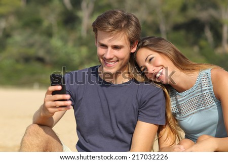 Happy teenager couple sharing social media on the smart phone outdoors                  - stock photo