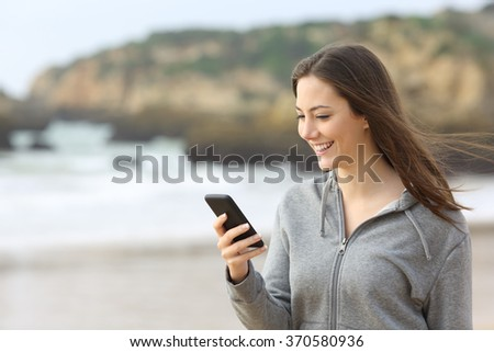 Happy teenager female texting messages or reading chat in a smart phone on the beach with the wind moving her hair - stock photo