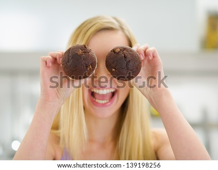 Happy teenager girl holding chocolate muffins in front of face - stock photo