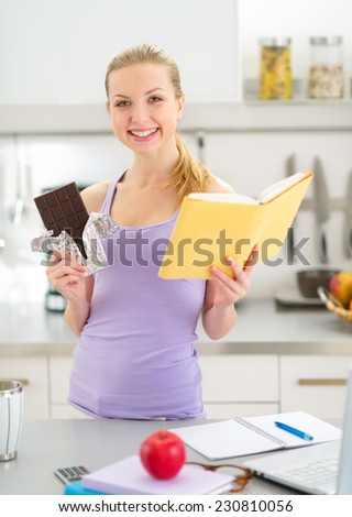 Happy teenager girl reading book and eating chocolate - stock photo