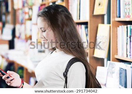 Happy teenager girl studying in library - stock photo