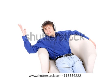 happy teenager in headphones sitting in a chair on the white background - stock photo