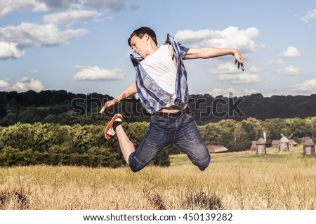 Happy teenager jumps up on the field on a sunny day - stock photo