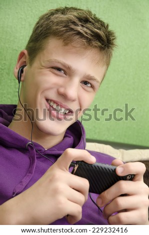 Happy teenager listening to music on his smart phone with ear buds selective focus - stock photo