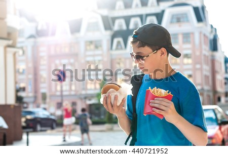 Happy teenager on the streets of the city with food in the hands of