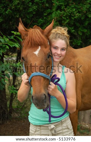 Happy teenager showing off her brand new horse - stock photo