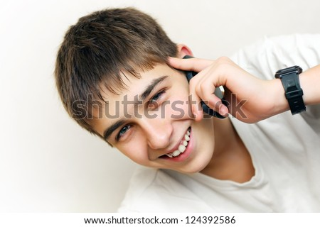 Happy Teenager speaking on the Phone. On the White Wall Background