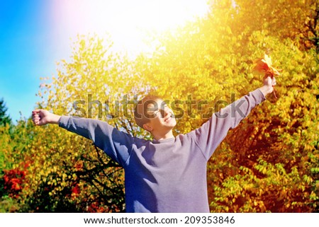 Happy Teenager with Autumnal Leafs at the Park - stock photo