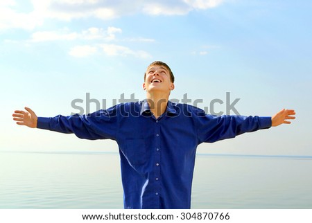 Happy Teenager with Hands Up on the Seaside Background - stock photo