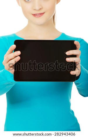 Happy teenager woman holding a tablet. - stock photo