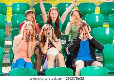Happy teenagers cheer for the team during game - stock photo
