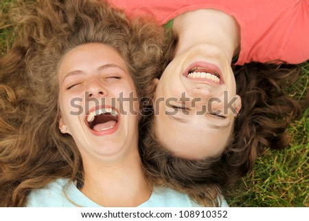 Happy teenagers friends lying on a grass laughing in a park - stock photo