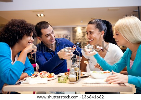 Happy teenagers having fun while lunch at restaurant - stock photo