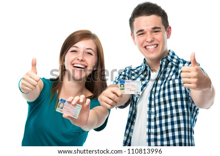 happy teens showing their driving license - stock photo