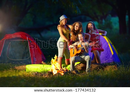 happy teens together around camp fire - stock photo