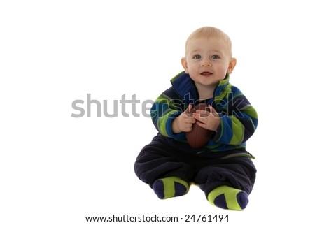 Happy teething baby holds small football - stock photo