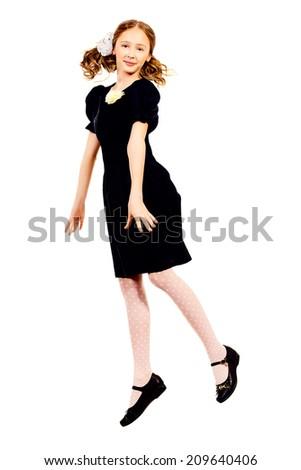 Happy ten years schoolgirl jumping for joy. Isolated over white. Full length portrait. - stock photo