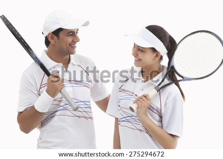 Happy tennis players looking at each other while holding rackets isolated over white background - stock photo