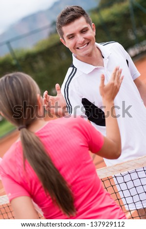Happy tennis trainer giving high five to a woman