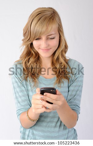 Happy Texting. Thirteen year old girl smiling as she reads a text message on her smartphone. Note: Not Isolated. - stock photo