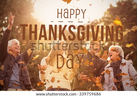 Happy thanksgiving against happy family throwing leaves around - stock photo