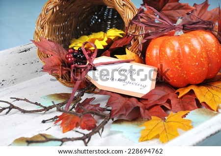 Happy Thanksgiving cornucopia with Autumn Fall leaves, pumpkin, sunflower and berries on white shabby chic tray against a pale blue background. Close up.