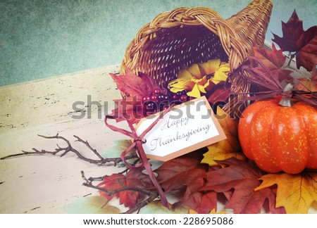 Happy Thanksgiving cornucopia with Autumn Fall leaves, pumpkin, sunflower and berries on white shabby chic tray against a pale blue background, with retro grunge filter. - stock photo