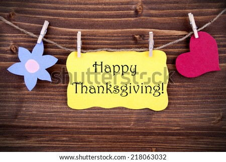 Happy Thanksgiving Greetings on a Yellow Label with a Flower and a Heart Symbol Hanging on a Line - stock photo